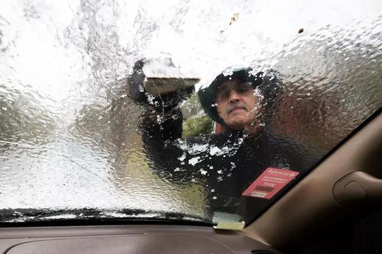 ▲1月3日,乔治亚州一名车主正在去挡风玻璃上的结冰 图据美联社
